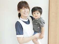 子供を抱き上げる保育士の写真